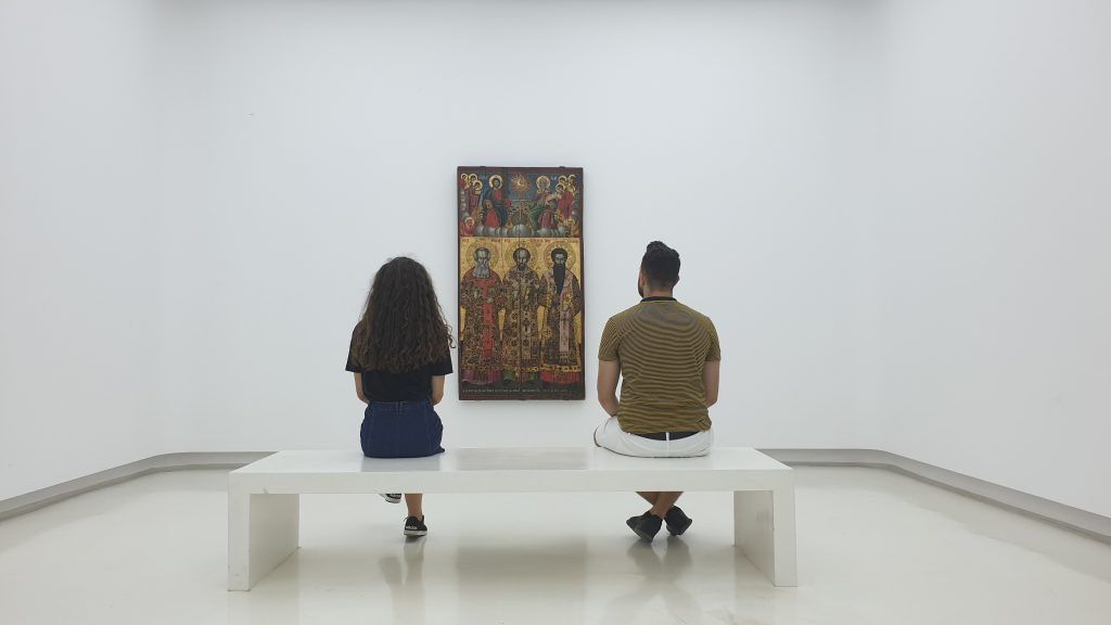 Visiting An Art Gallery, Couple sat on a white bench in a white room, looking at a painting.